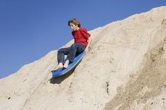 Extreme Childhood Fun. A young kid sliding down sand dunes Stock Photo
