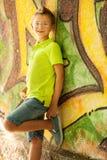 Young kid standing near graffiti wall Royalty Free Stock Photos