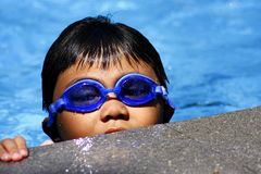 Young kid with swimming goggles in a pool. Photo of a young kid with swimming goggles at the edge of a swimming pool Stock Image