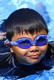 Young kid with swimming goggles in a pool. Photo of a young kid with swimming goggles at the edge of a swimming pool Stock Photos