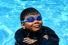 Young kid with swimming goggles smiling while in a swimming pool. Royalty Free Stock Photos