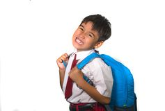 young kid in uniform carrying bag full of books upset and complaining about the weight of the backpack in lazy schoolboy unhappy royalty free stock photography