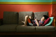 Young kid using a tablet or smartphone on a couch Stock Photography