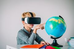 Young kid with virtual reality headset touching earth globe, technology. Young kid with virtual reality headset ing earth globe, technology in education royalty free stock image