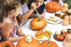 Young kids carving Halloween jack-o`-lanterns stock photo