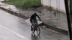 Young kids cycling in rain outdoors n