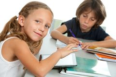 Young kids doing schoolwork together at desk. Royalty Free Stock Image