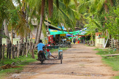 Young kids driving tricycle motorcycle on unpaved street in Cham Royalty Free Stock Images