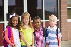 Young Kids going to School. Young kindergarten age kids standing in front of their school getting ready to go inside Royalty Free Stock Image