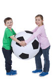 Young kids with huge soccer ball Royalty Free Stock Photography
