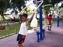 Young kids play at an outdoor park with gym equipments Stock Image