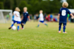 Young kids playing soccer. Outside during summer time. All players are blurred Royalty Free Stock Photography