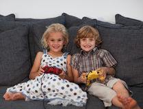 Young Kids playing Video Games. On a sofa at home Royalty Free Stock Photography