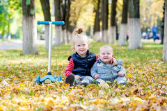Young kids sit on autumn leafs Royalty Free Stock Photos