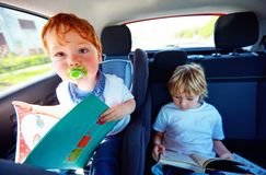 Young kids sitting on back seat, reading book while traveling in the car. Two young kids sitting on back seat, reading book while traveling in the car royalty free stock photos