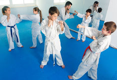 Young kids sparring in pairs in karate class. Young kids sparring in pairs to practice new moves in karate class Stock Image