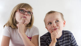 Young kids thinking. Two young kids holding their chins while thinking of how to solve lifes problems stock photo