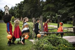 Young kids trick or treating during Halloween stock images