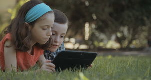 Young kids using a tablet computer outdoors on the grass stock video footage