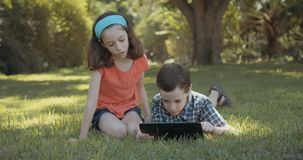 Young kids using a tablet computer outdoors on the grass
