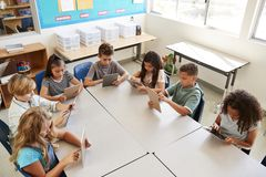Young kids using tablets in school lesson, elevated view royalty free stock photo
