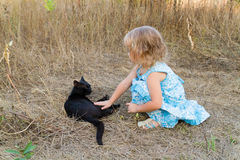 Young kind girl and black cat. Royalty Free Stock Image
