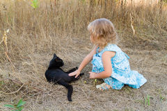Young kind girl and black cat. Stock Photo