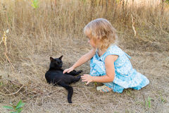Young kind girl and black cat. Stock Photography