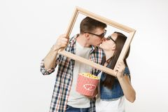 Young kissing couple, woman and man in 3d glasses and casual clothes watching movie film on date, holding bucket of stock photos