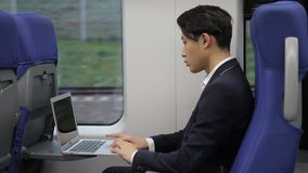 Young Korean businessman with laptop is riding in train. Korean man is sitting and looking attentively at screen of silvery device, tapping on keyboard with stock video