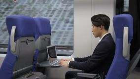 Young Korean businessman is working with laptop sitting in train. Korean guy looks at screen of silvery device carefully, tapping on keyboard with fingers stock video