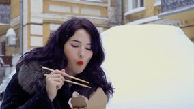 Young korean eats a noodles on the street during snowfall. Businesswoman has a break on the work and eating the noodles on the street because she`s hurry up to stock video footage
