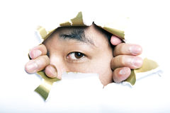 Young Korean man looking through ripped paper hole Stock Photography