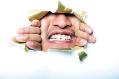 Young Korean man looking through ripped paper hole Royalty Free Stock Photography