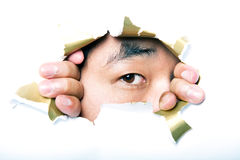 Young Korean man looking through ripped paper hole Royalty Free Stock Photo
