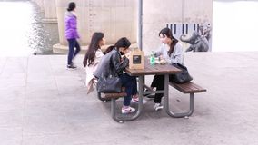 Young korean students girls eating noodles outside, Seoul, South Korea. Seoul, South Korea - March 28 2018: Funny young korean students girls eating traditional stock footage