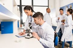 Young lab technicians working with microscope and taking notes on analysis. On clipboard royalty free stock image