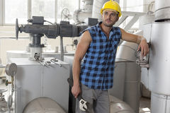 Young labor holding wrench while leaning on industrial machine Royalty Free Stock Image