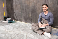 Young laborer sitting on floor with digital tablet and smiling at camera. Handsome young laborer sitting on floor with digital tablet and smiling at camera Royalty Free Stock Photos