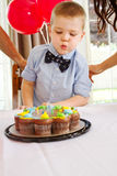 Young lad blowing out candles at birthday party Royalty Free Stock Images