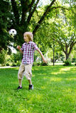 Young lad kicking soccer ball Royalty Free Stock Images