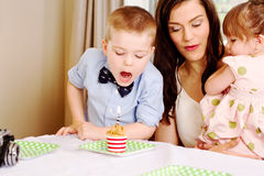 Young lad poised to blow out candle. Young lad ready to blow out candle with Mom and sister looking on Stock Images