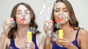 Young ladies blowing bubbles stock video footage