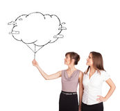 Young ladies holding cloud balloon drawing Stock Photo