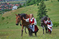Young ladies with horses. Young ladies in traditional szekler clothes with beautiful horses in Csiksomlyo (Sumuleu Ciuc) - Romania, waiting for Holy mass. Photo Royalty Free Stock Photos