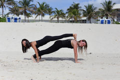 Young ladies performing yoga on the sand Royalty Free Stock Photo