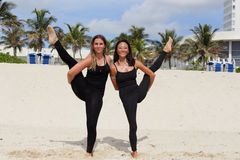 Young ladies performing yoga on the sand Stock Photos