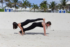 Young ladies performing yoga on the sand Royalty Free Stock Image
