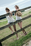 Young ladies are posing. Two beautiful young ladies are posing at paddock Stock Image
