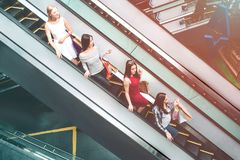 Young ladies are riding on escalator. They are standing one after another. Each of them has shopping bags. They are royalty free stock image